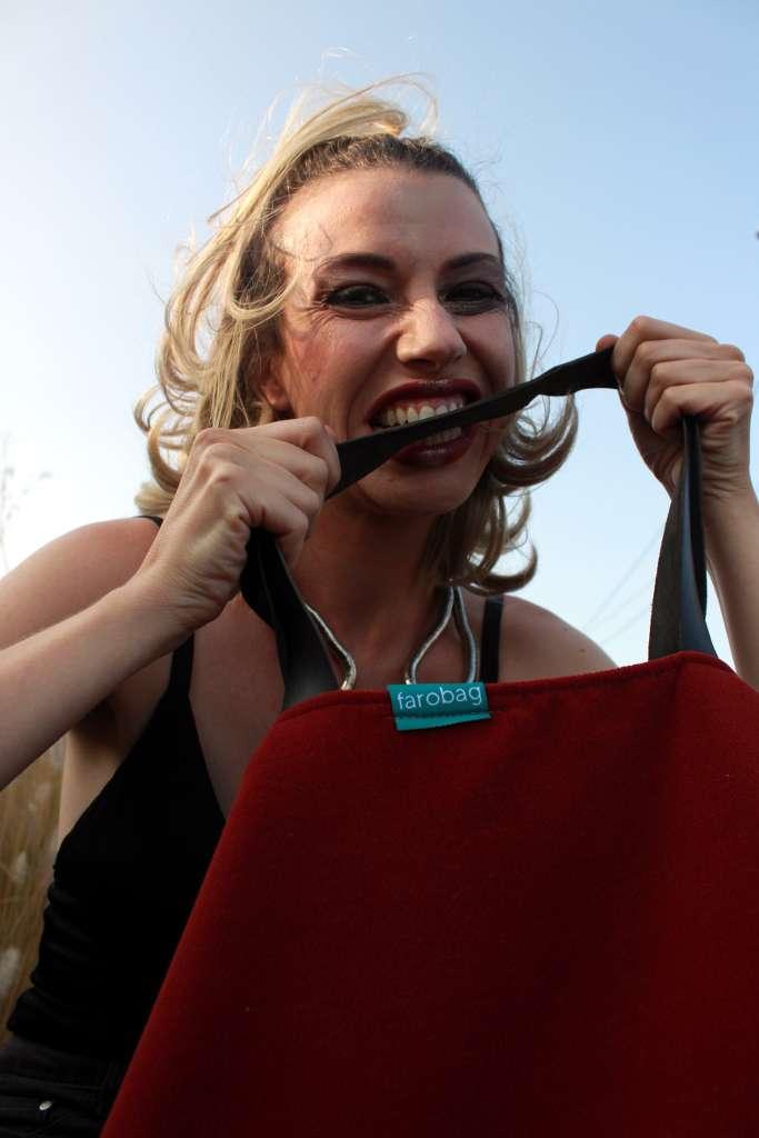 Modelo mordiendo el asa de un bolso de tela tipo travelbag XL de la serie ópalo de Farobag