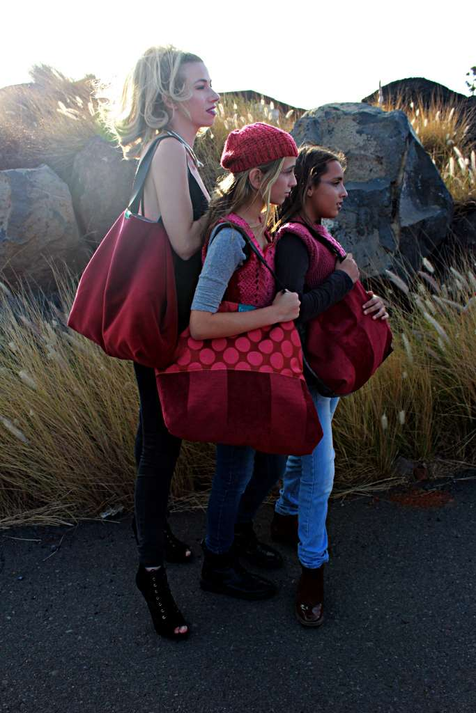 Tres modelos con bolso de tela tipode la serie ópalo: un travelbag XL y dos travelbag