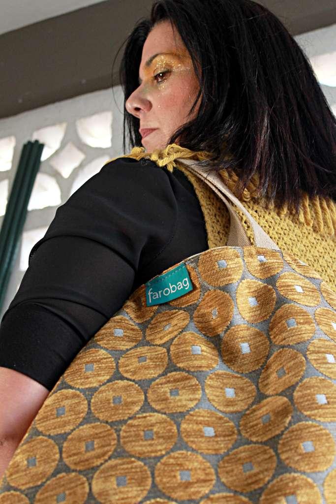 Modelo con bolso de tela tipo travelbag XL de la serie ámbar de Farobag