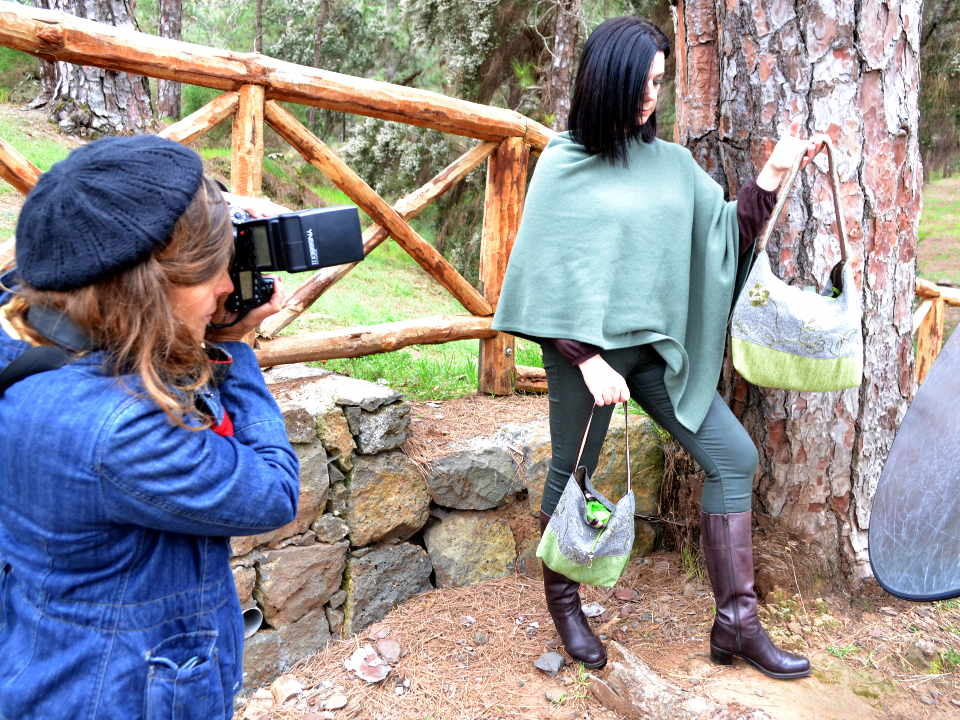 Fotografa con cámara y modelo con bolsos