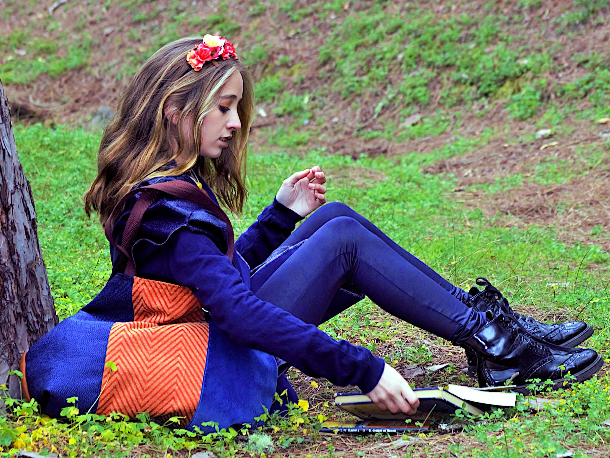 Mujer sentada en el suelo al pie de un árbol con un bolso de tela en el hombro