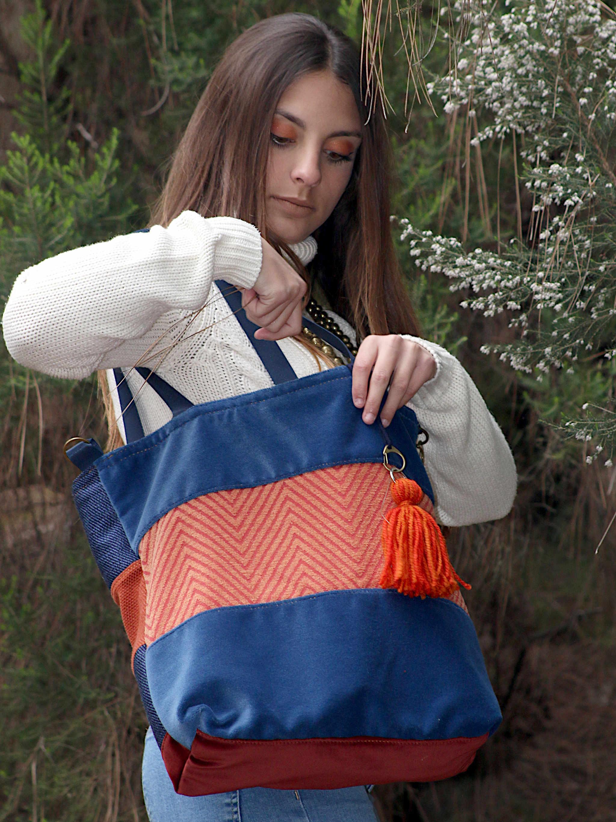 Mujer bajo un árbol mirando el contebido del bolso de tela que lleva en el hombro