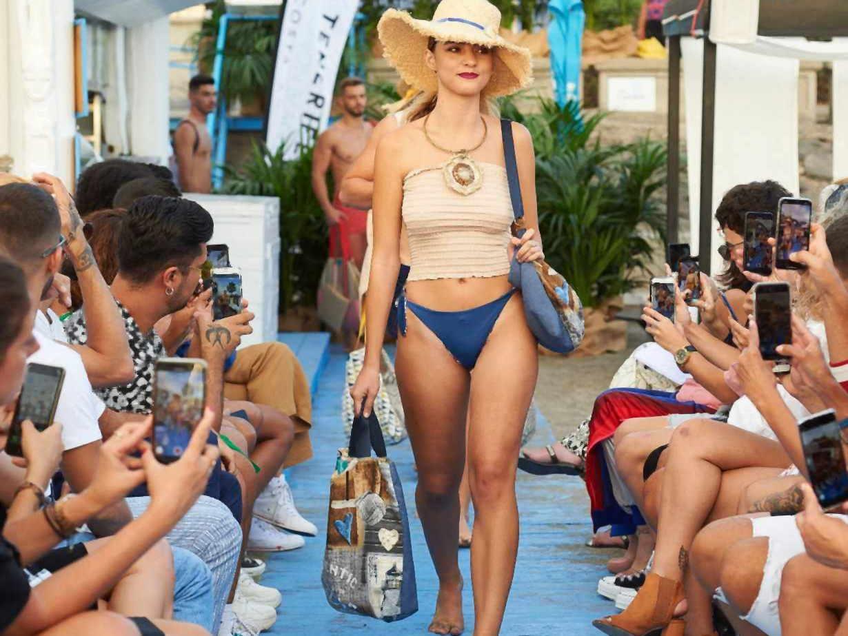 Modelo en la pasarela de moda de Farobag con bolsos de playa y sombrero