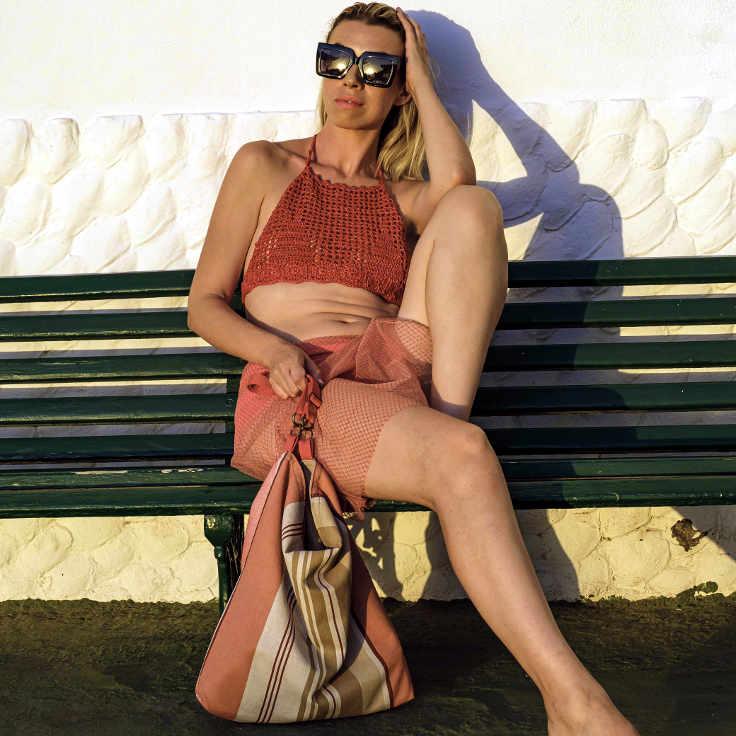 Modelo sentada en un banco con un bolso de tela de farobag