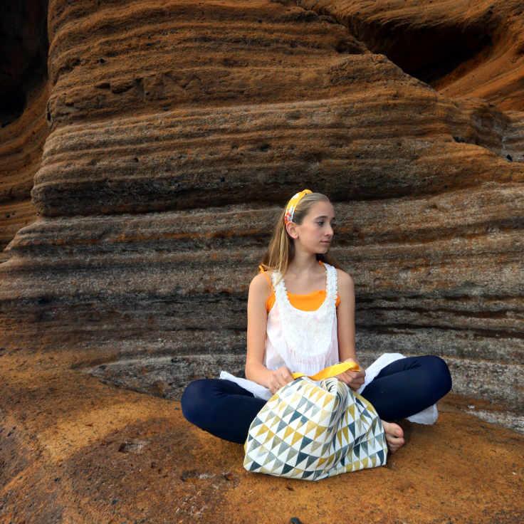 Modelo sentada en la roca con bolso de tela de la serie Tabaiba de Farobag